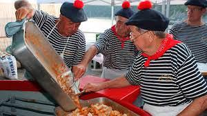 Uomini in costume tradizionale impegnati a preparare e servire il BAGNUN DI ACCIUGHE